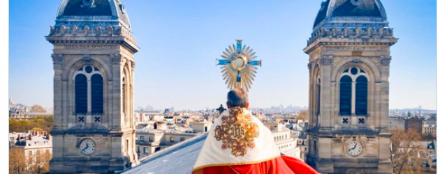 Priest carries Blessed Sacrament on rooftop of his Paris church…