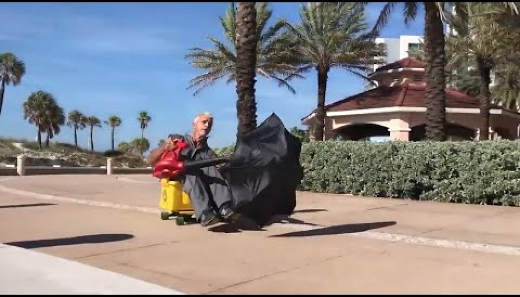 Florida janitor rides his mop bucket, umbrella and leaf blower into well-earned glory…